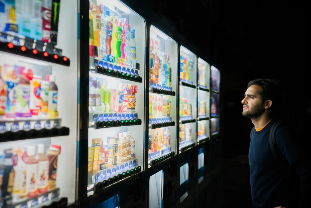 a man choosing a product from a wall of coolers in a supermarket