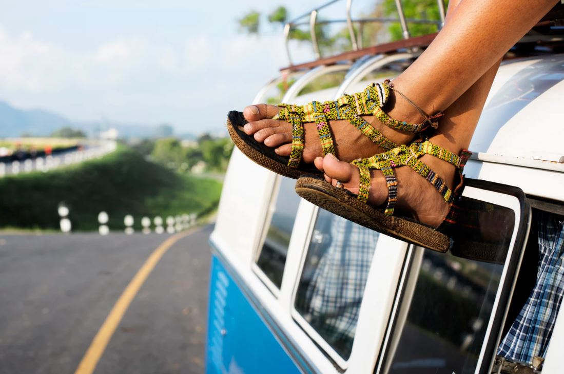 woman's sandaled feet hanging off a van roof driving down a road