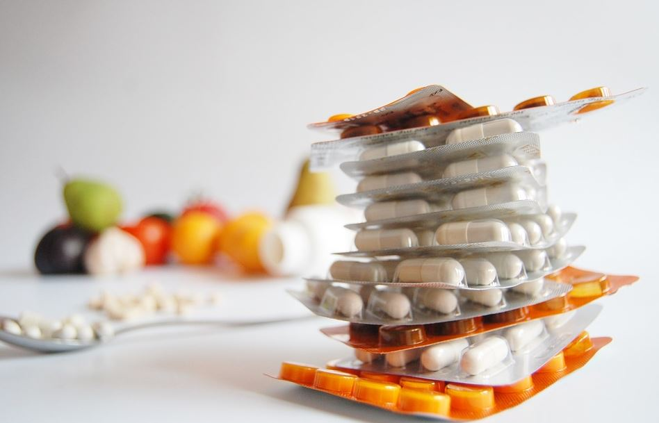 stack of supplements in orange and silver blister packages