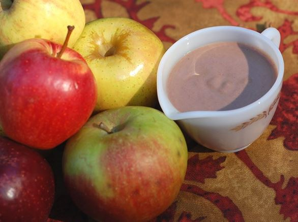 Pitcher of Easy Slow Cooking's Apple Spice Creamer Next to a Mound of Fresh Apples