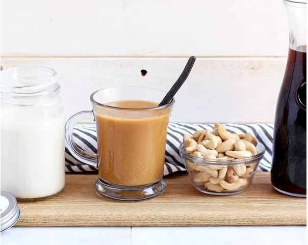 Wooden Skillet's Cashew Creamer, Creamed Coffee, Cashews and Coffee Tumbler Lined Up on a Kitchen Counter