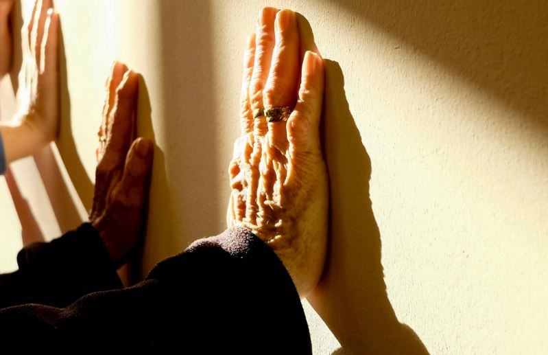 hands pressing against a light yellow wall