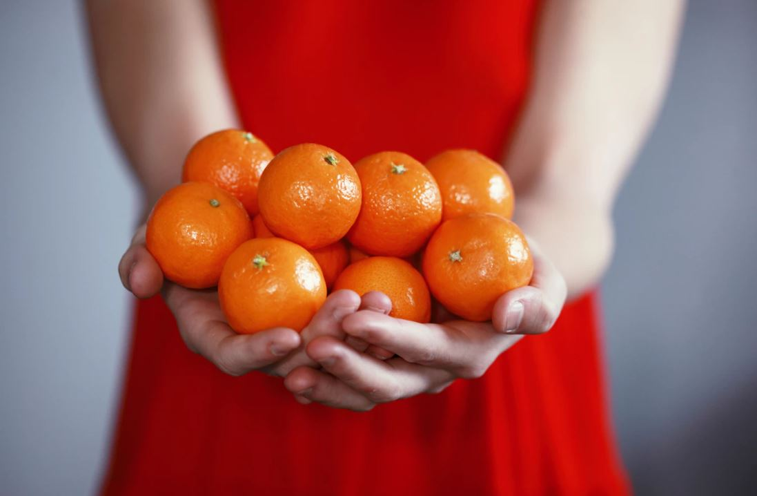 Woman in a red dress holding out mandarin oranges