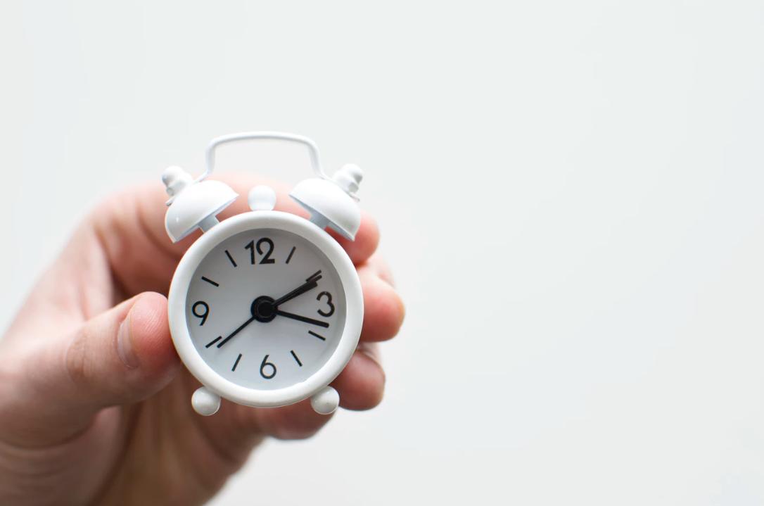 Man's hand holding a mini alarm clock