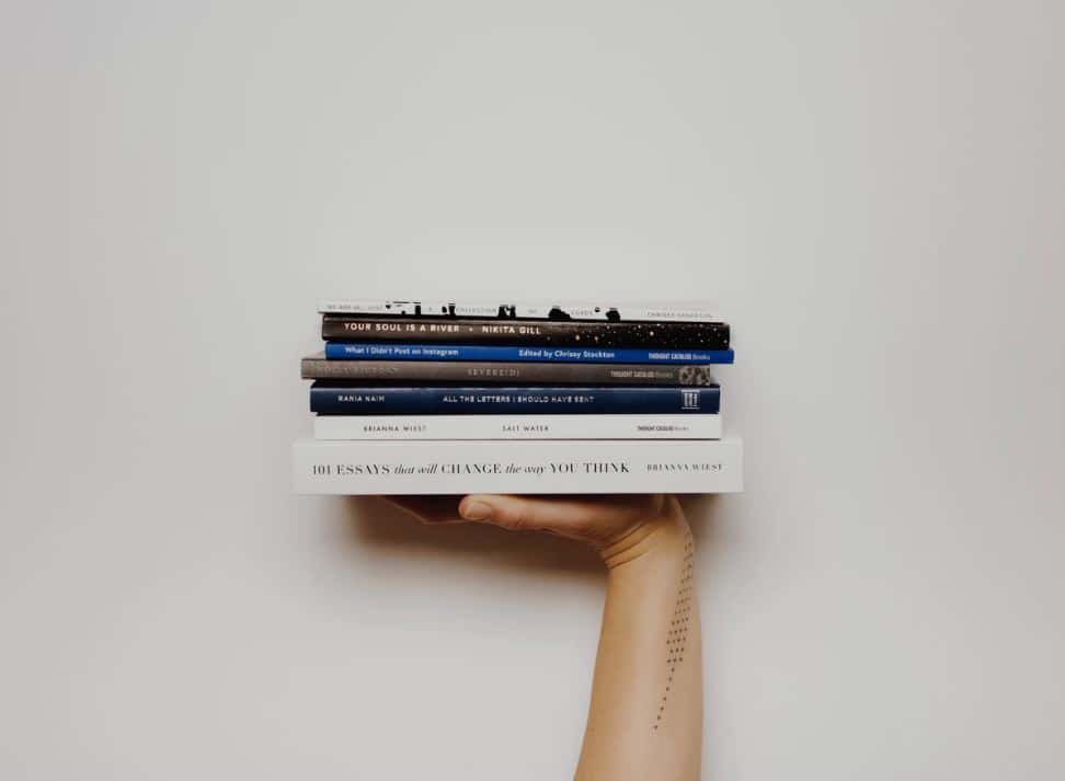hand holding up a stack of books