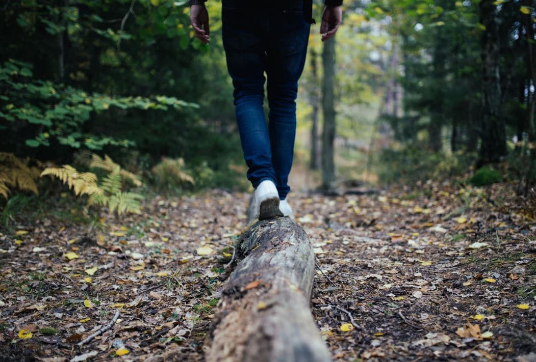 man walking along a log in the woods