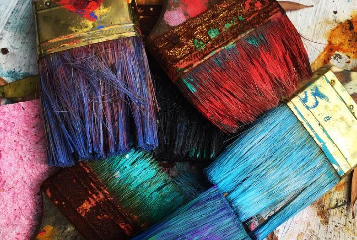 paint brushes covered in brightly colored paint