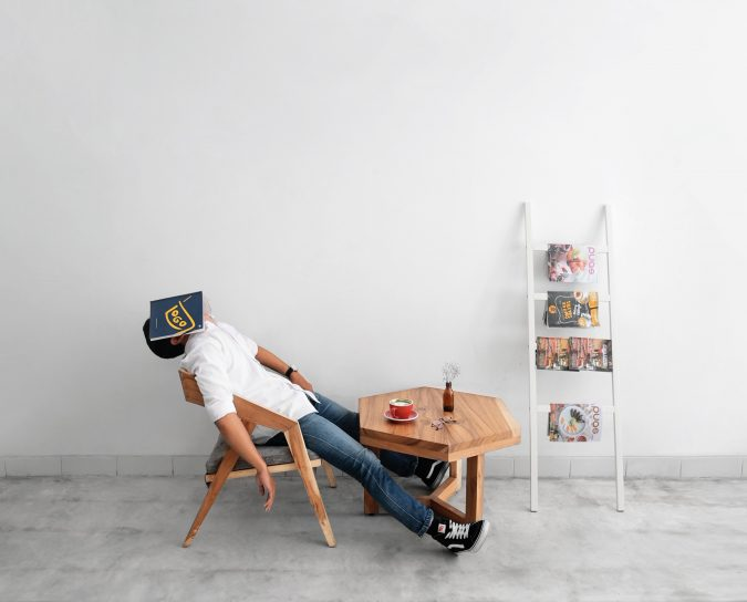 guy asleep on a chair with a book covering his face