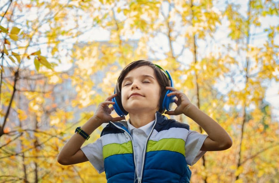Young Boy Wearing Headphones in the Woods