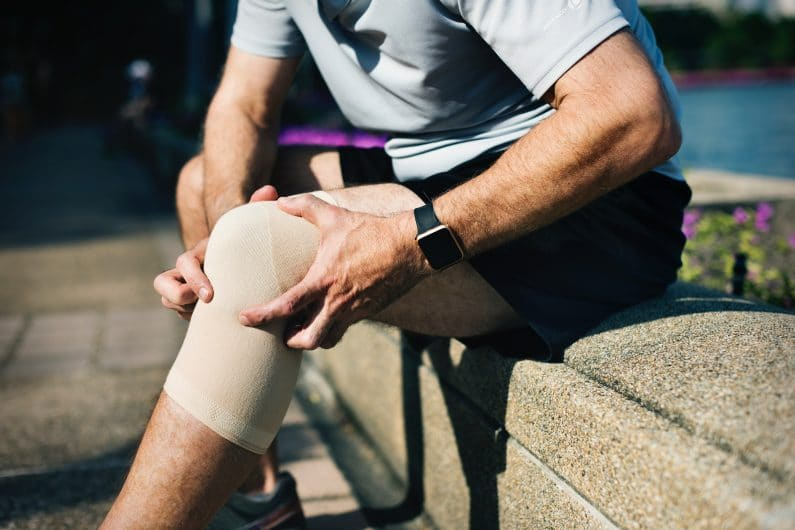 Man rubbing his bandaged knee