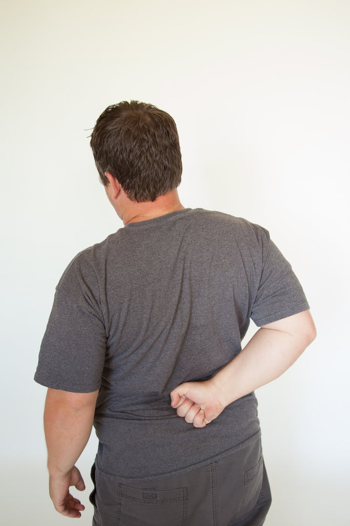 Man bracing painful lower back with arm