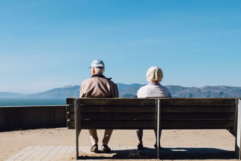 Older Couple Sitting On Bench Overlooking the Ocean