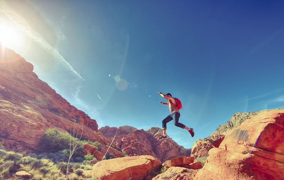 Man jumping off a boulder in the desert sunshine