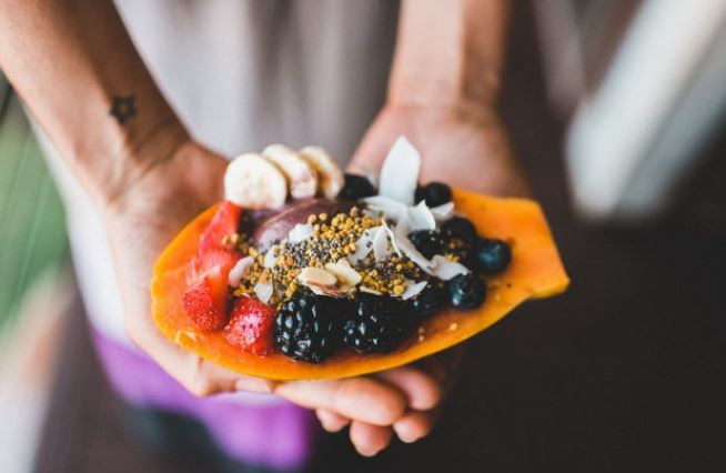Foods Rich in Digestive Enzymes: Woman holding a papaya filled with other fruits