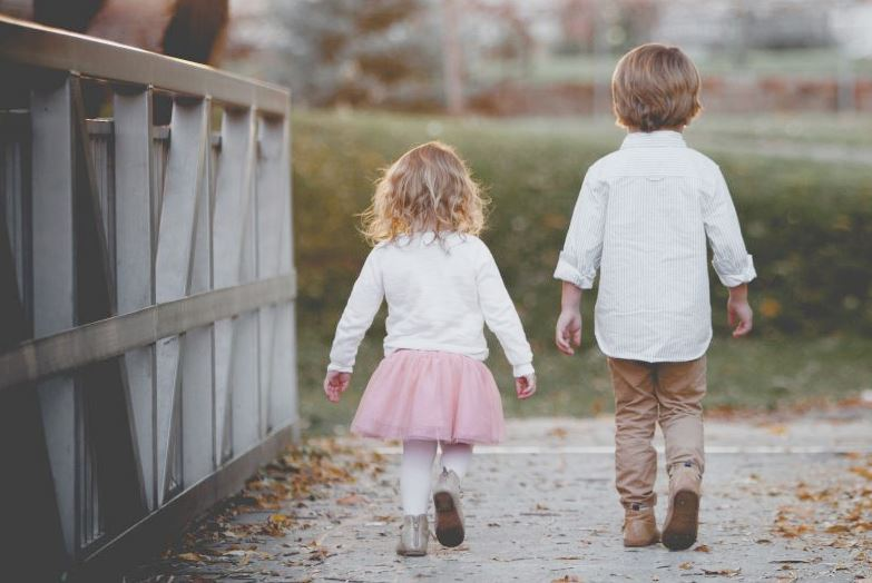 Boy and girl walking on a bridge