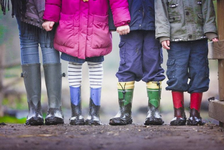 Four kids on a bridge wearing rain boots