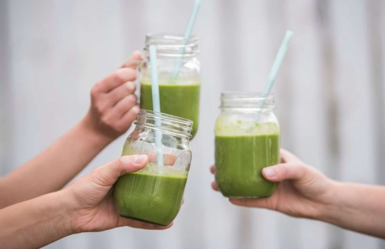 Three people holding green smoothies