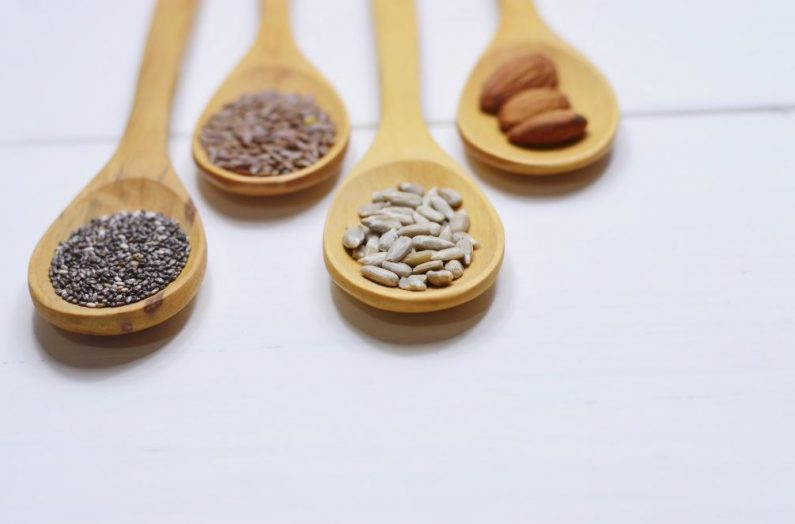 Flaxseeds, chia seads, almonds, and sunflower seeds on wooden spoons