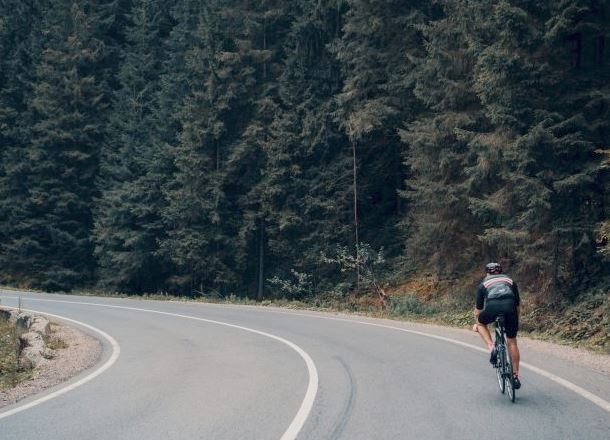 Cyclist on a wooded highway