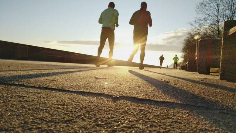 Four people running in the sunrise