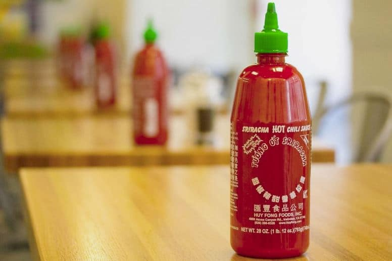 Sriracha bottles on restaurant tables