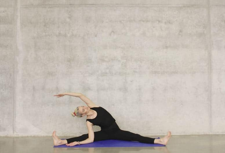Woman stretching on purple yoga mat