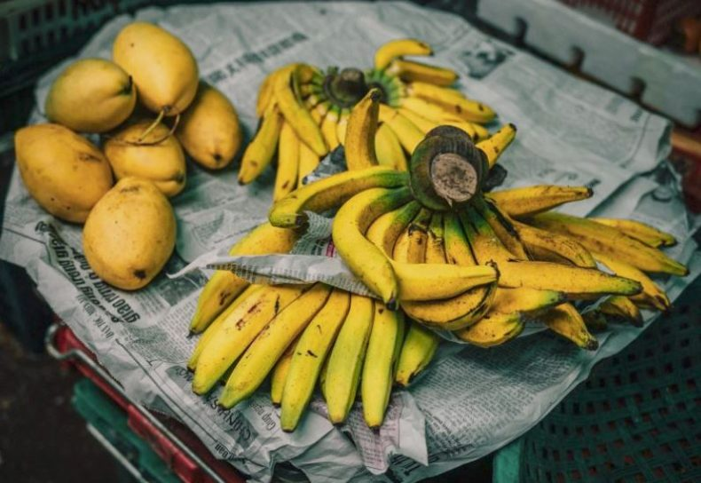 Potassium-rich bananas and papayas on newspapers