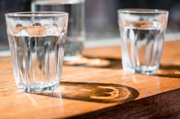 Glasses of chlorinated water on a wooden table